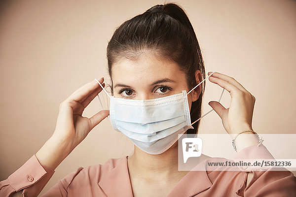 Junge Frau zieht Mundschutz an