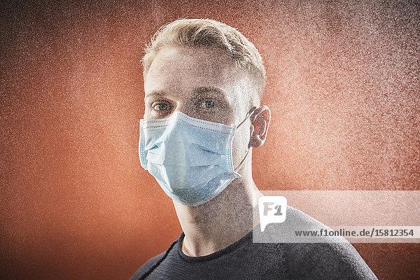 Junger Mann mit Mundschutz blickt in Kamera
