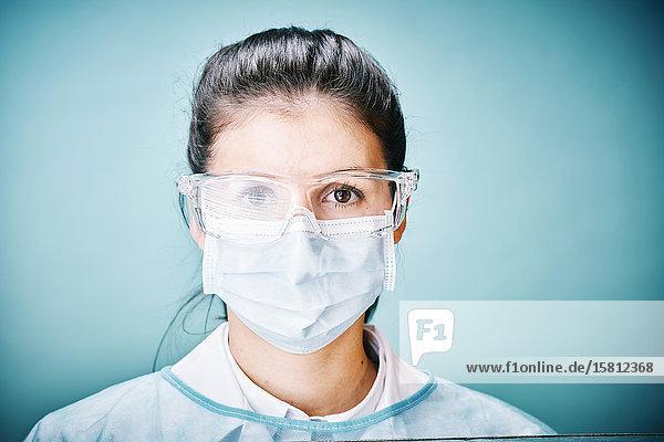 Ärztin mit Schutzbrille und Mundschutz blickt in Kamera