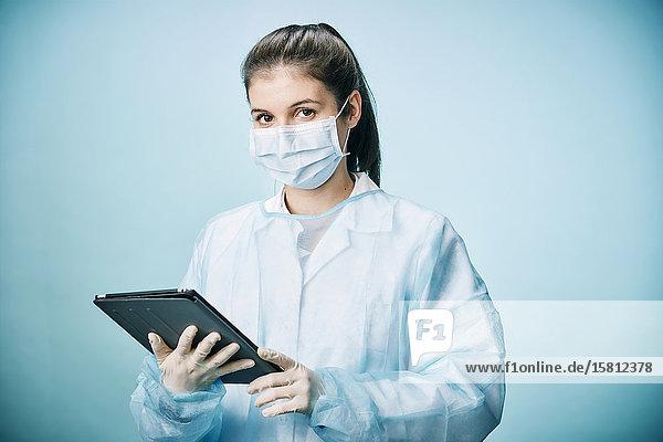 Ärztin mit Mundschutz und Tablet-PC blickt in Kamera