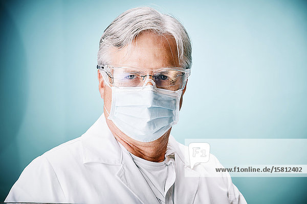 Grauhaariger Arzt mit Schutzhandschuhen und Schutzbrille blickt in Kamera