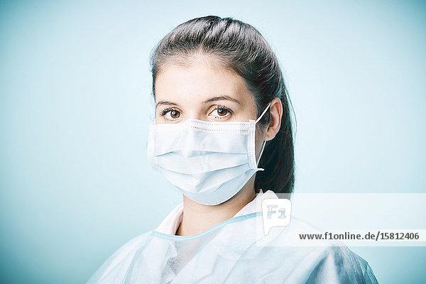 Krankenschwester mit Mundschutz blickt in Kamera