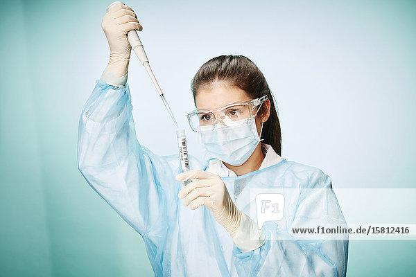 Laborantin füllt Probe mit Coronavirus in Reagenzglas