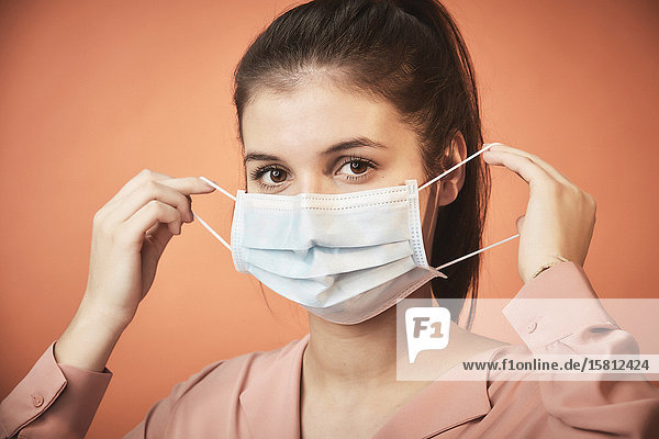 Young woman puts on face mask
