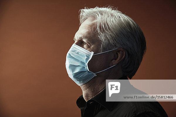 Grauhaariger Mann mit Mundschutz im Profil