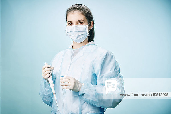 Laborantin mit Mundschutz  Pipette und Reagenzglas schaut in Kamera
