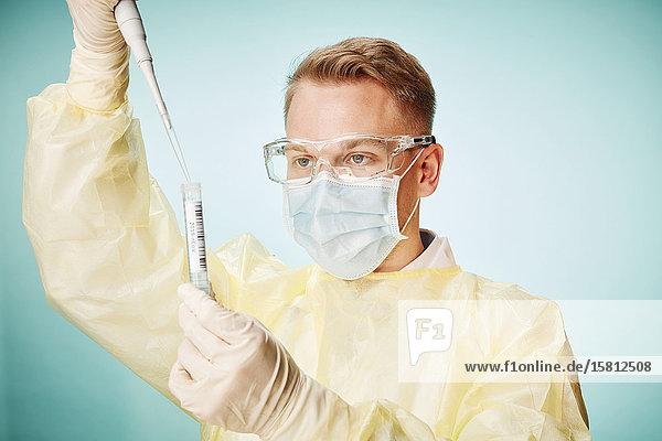 Junger Laborant mit Pipette füllt Coronavirus Probe in Reagenzglas