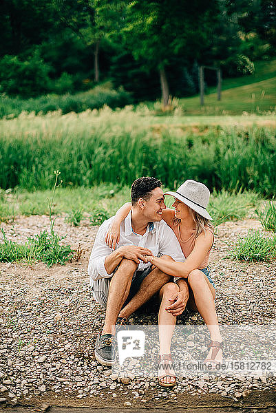Young couple sitting on a riverbank  smiling at each other and hugging.