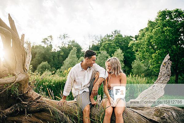 Junges Paar sitzt auf einem umgefallenen Baum am Flussufer und lächelt sich an.