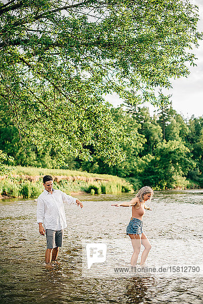 Young couple standing ankle deep in a river.