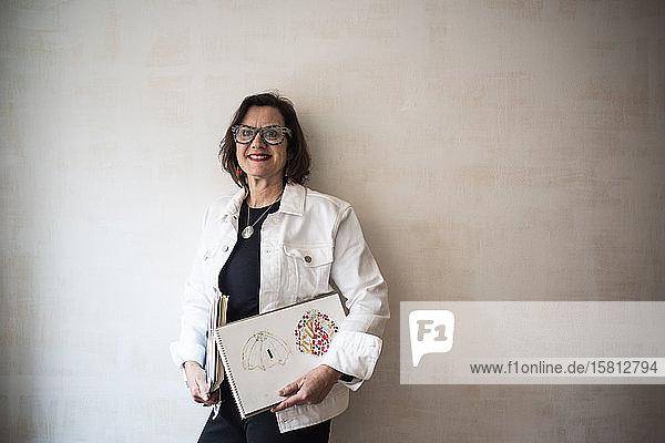 Bildnis einer brünetten Frau mit Brille und weißer Jeansjacke  die Skizzenbücher des Künstlers in der Hand hält.