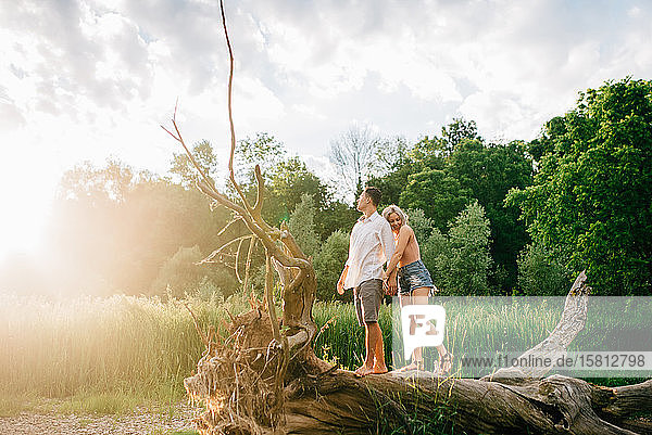 Junges Paar steht auf einem umgefallenen Baum am Flussufer  hält sich an den Händen und lächelt.