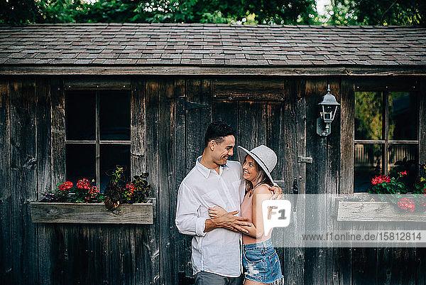 Junges Paar steht vor einer Holzhütte  umarmt sich und lächelt einander an.