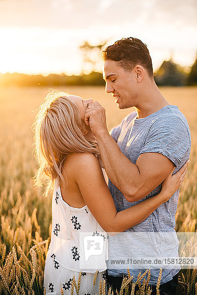 Smiling young couple standing in golden wheat field  smiling at each other.