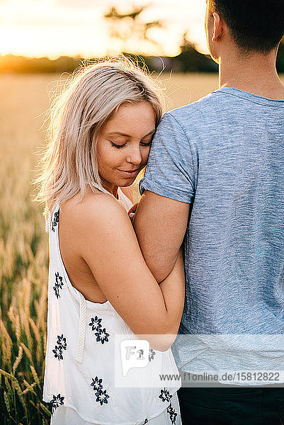 Smiling young couple standing in golden wheat field  hugging.