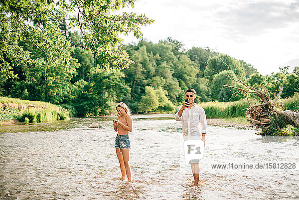 Young couple standing ankle deep in a river  using their mobile phones to take pictures.