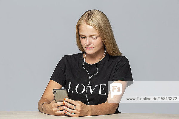 Young woman in love t-shirt listening to music with mp3 player and headphones