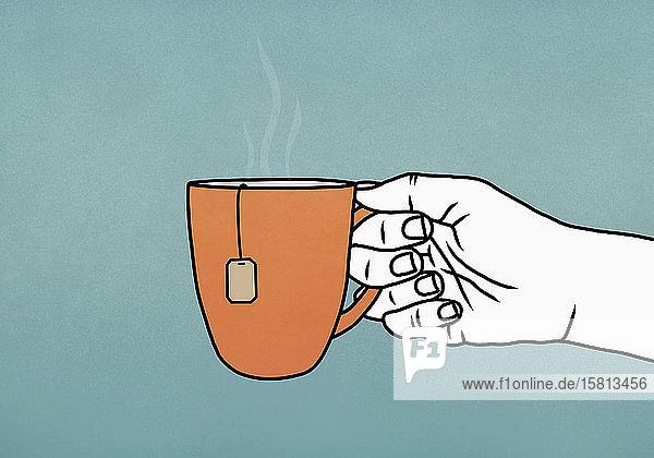 Hand hält Becher mit heißem Tee