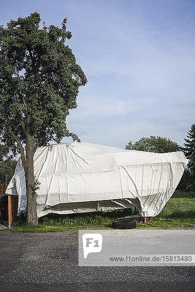Covered boat in sunny backyard