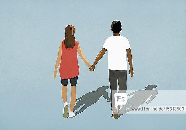 Multiethnisches Paar hält sich an den Händen und geht spazieren