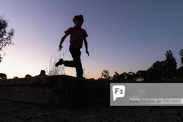 Silhouette Junge läuft gegen Dämmerung Himmel