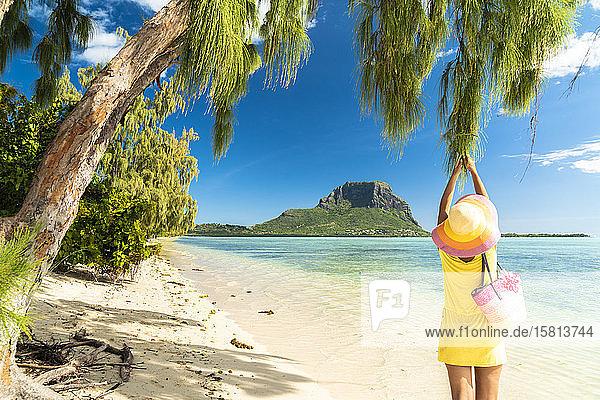 Woman having fun under a tropical tree on sandy beach  Ile aux Benitiers  La Gaulette  Le Morne Brabant  Mauritius  Indian Ocean  Africa