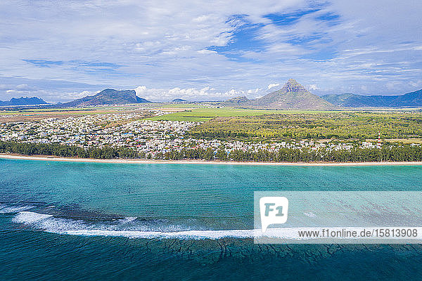 Aerial view by drone of waves crashing on Flic en Flac beach with Piton de la Petite Riviere Noire mountain  Mauritius  Indian Ocean  Africa