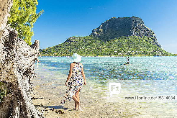 Woman on tropical beach looking at paddleboard in the lagoon  La Gaulette  Le Morne Brabant  Black River  Mauritius  Indian Ocean  Africa