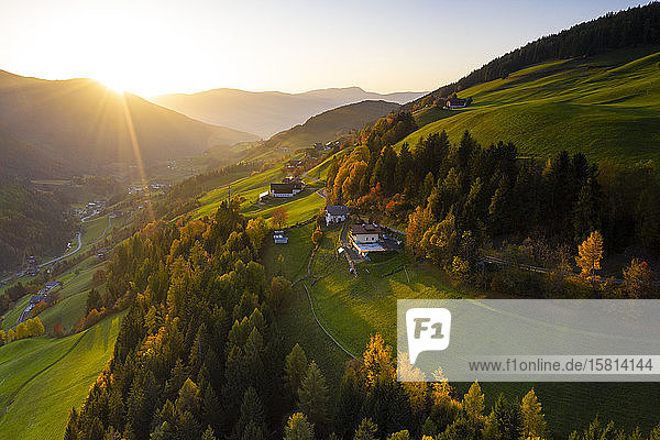 Sunbeam at sunset lighting the warm colors of autumn in Funes Valley  aerial view  Dolomites  Bolzano province  South Tyrol  Italy  Europe