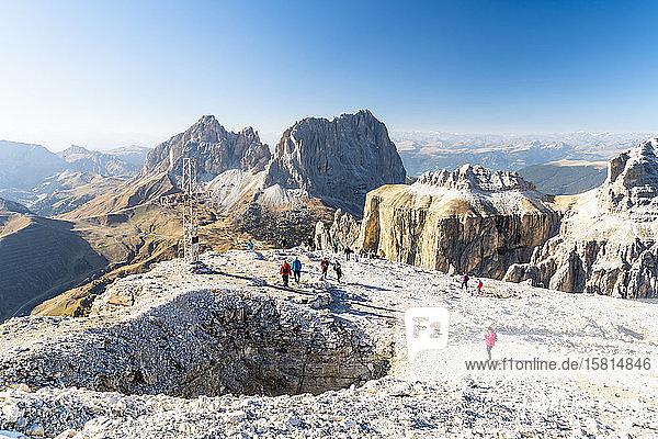 Hikers admiring Sella Pass  Sassolungo and Sassopiatto from top of Sass Pordoi  Dolomites  Trentino  Italy  Europe