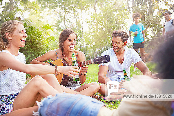 Young friends laughing  hanging out drinking and playing guitar in summer park