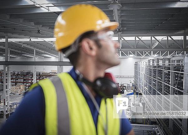 Male worker looking away on platform in factory Male worker looking away on platform in factory