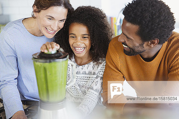 Multi-ethnic family making healthy green smoothie in blender