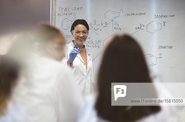 Smiling female science teacher leading lesson at whiteboard in classroom