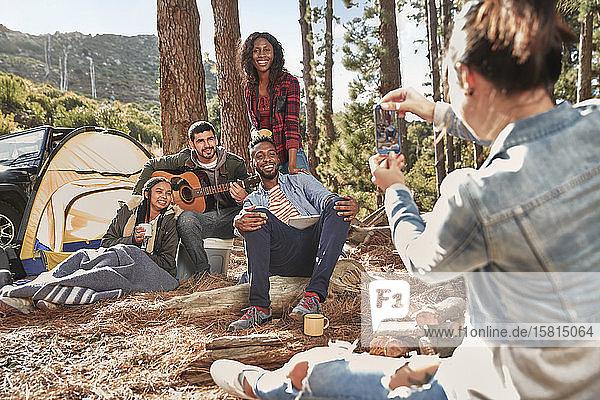 Junge Frau mit Fotohandy  die ihre Freunde auf einem Campingplatz im Wald fotografiert