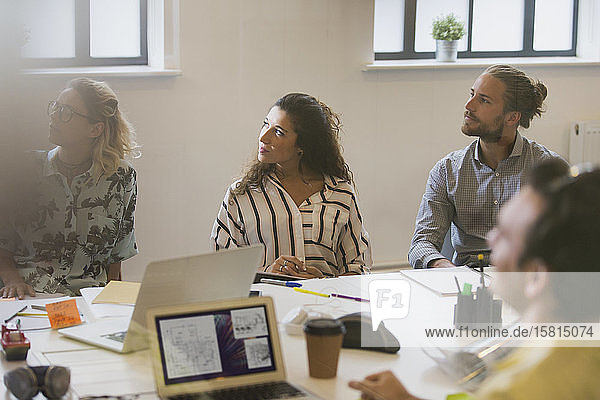 Attentive designers listening in conference room meeting