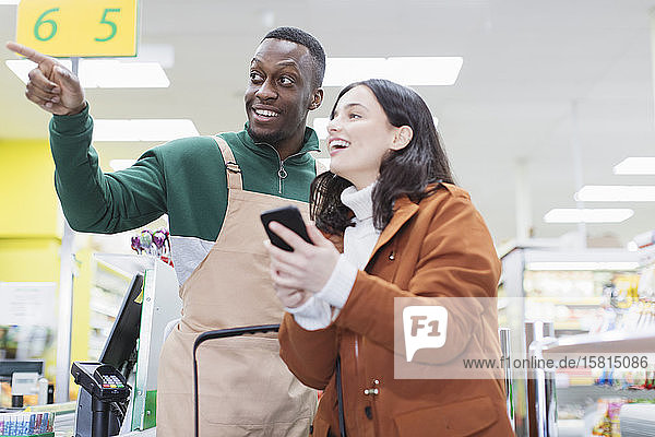 Male grocer helping customer in supermarket