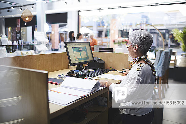 Senior woman working at computer in home decor shop