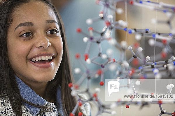 Curious  smiling girl student examining molecular structure Curious, smiling girl student examining molecular structure