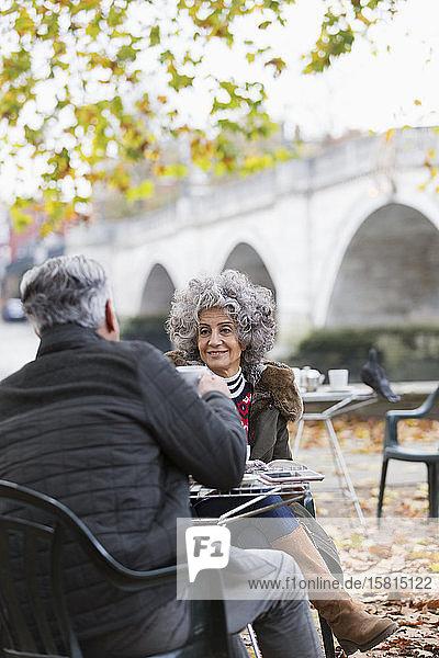 Smiling active senior couple enjoying coffee at autumn park cafe
