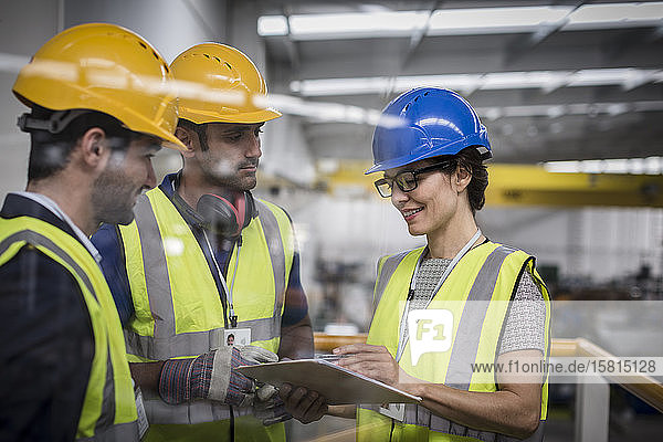 Supervisors with clipboard talking on platform in factory