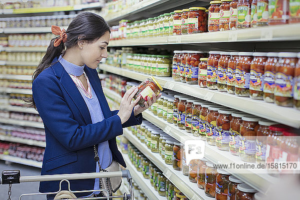 Woman reading label on jar in supermarket