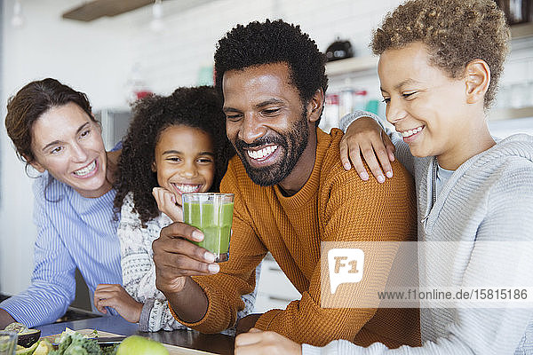 Multi-ethnic family drinking healthy green smoothie in kitchen Multi-ethnic family drinking healthy green smoothie in kitchen