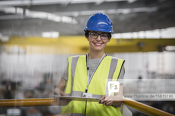 Portrait smiling  confident female worker with clipboard on platform in factory