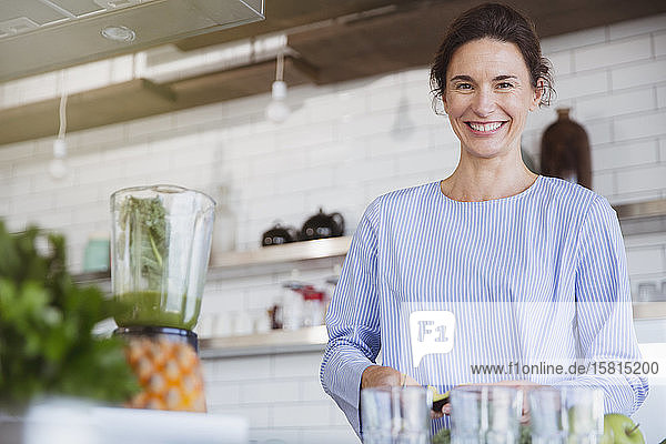 Portrait smiling  confident brunette woman preparing healthy green smoothie in blender in kitchen