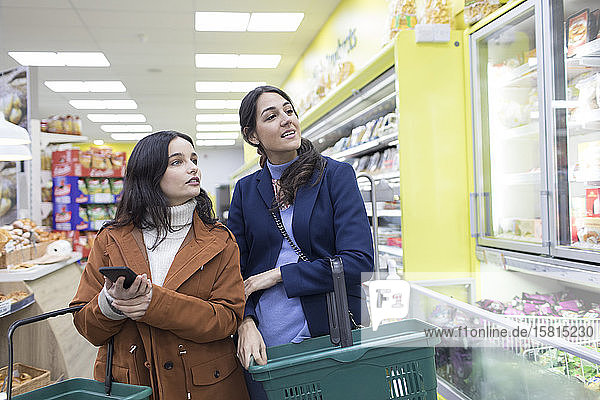 Young women grocery shopping in supermarket