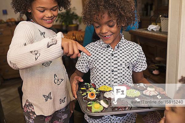 Fröhliches Geschwisterpaar mit dekorierten Halloween-Cupcakes