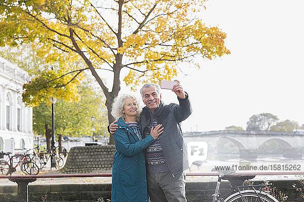 Älteres Paar macht Selfie vor einem Herbstbaum