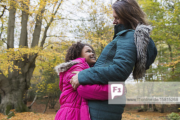 Happy mother and daughter hugging in autumn woods