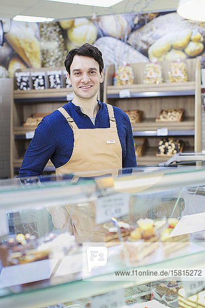 Portrait confident man working at bakery display case in supermarket